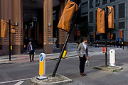 A leaning traffic light pole and covered others in a City of London street. Damaged perhaps by a vehicle that has crashed into the post and making it stand at an odd angle, it contradicts the stance of the man at the front, about to cross the road. The location is in the City of London, the heart of the capital's financial district and where roadworks have disabled the traffic lights covered with orange covers so pedestrians need to take care when crossing the street.