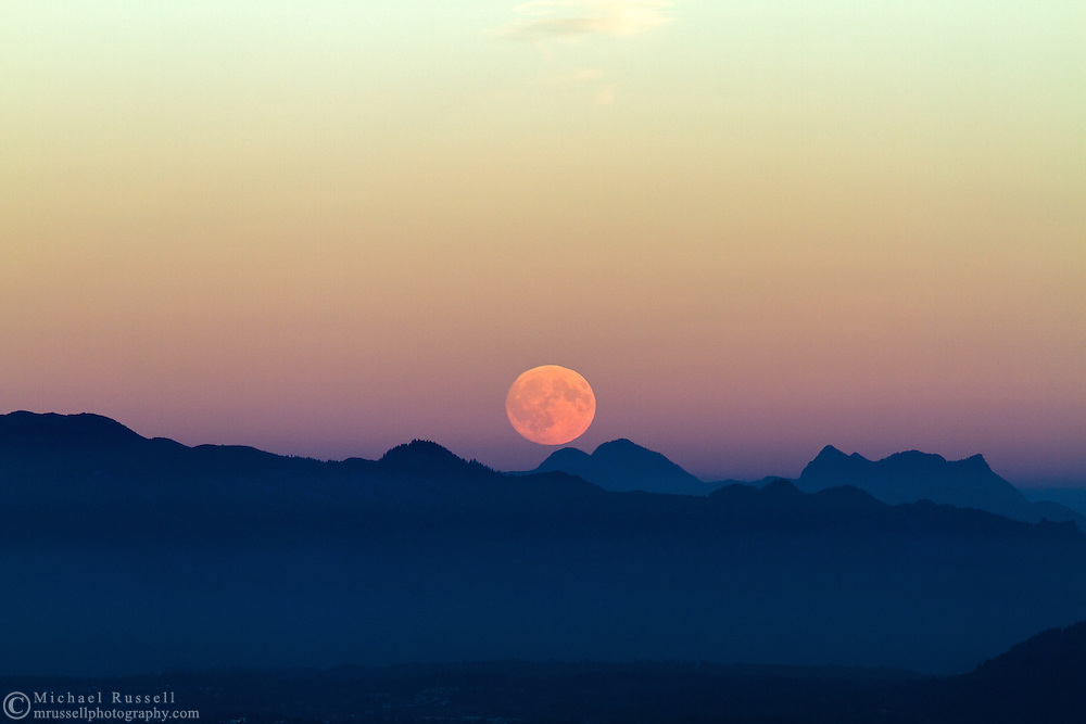 The moon rises into the Earth's Shadow over the peaks of the North Cascades mountains in Washington State, USA.  Peaks here include Round Mountain and  Mount Higgins.  Photographed from Mt. Erie Park in Anacortes, Washington.