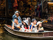 27 SEPTEMBER 2016 - BANGKOK, THAILAND:  A tourist boat goes through the floating market in Damnoen Saduak, Thailand. The market is famous because vendors cruise the canals around the market selling produce and tourist curios. It is one of the best known tourist attractions in Samut Songkhram province.     PHOTO BY JACK KURTZ