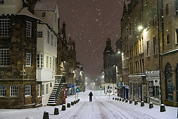 Edinburgh, Scotland, UK. 10 Feb 2021. Big freeze continues in the UK with heavy overnight and morning snow in the city. Pic; A cyclist rides carefully down the Royal Mile at John Knox House. Iain Masterton/Alamy Live news