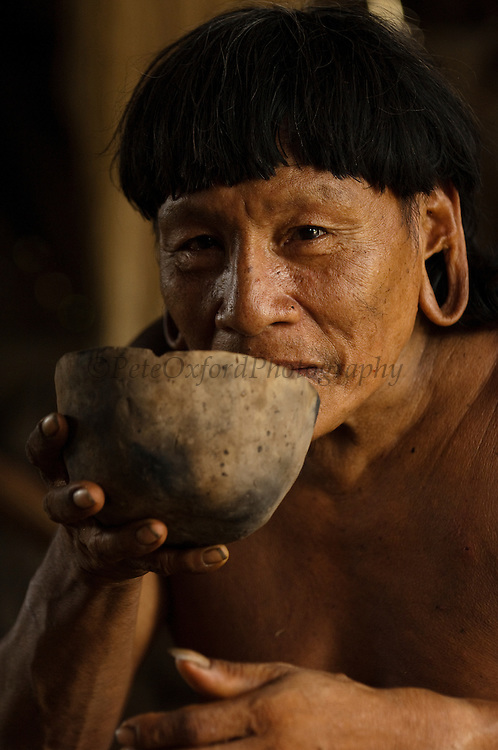Huaorani Indian - Menga Darita drinking chicha from a ceramic bowl. Gabaro Community. Yasuni National Park.<br /> Amazon rainforest, ECUADOR.  South America<br /> Chicha is a local 'beer' made from yucca. The Huaorani also make their own ceramic bowls.<br /> This Indian tribe were basically uncontacted until 1956 when missionaries from the Summer Institute of Linguistics made contact with them. However there are still some groups from the tribe that remain uncontacted.  They are known as the Tagaeri & Taromanani. Traditionally these Indians were very hostile and killed many people who tried to enter into their territory. Their territory is in the Yasuni National Park which is now also being exploited for oil.