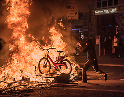 Jul 7, 2017 - Hamburg, Germany - A protester throws a public city bike into the burning barricade. Violent demonstrations against the Group of 20 summit meeting led to clashes between the police and protesters on the second consecutive night. (Credit Image: © Daniel Dohlus via ZUMA Wire)