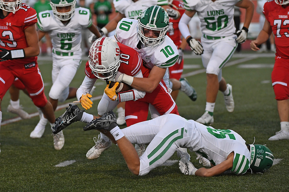 Taite Beachy #10 of the Moon Tigers is wrapped up for a tackle by Ryan Kovatch #10 of the South Fayette Lions in the first half during the game at Tiger Stadium on October 1, 2021 in Moon Township, Pennsylvania.
