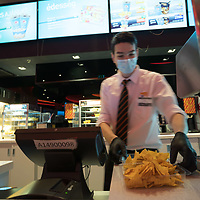 Employee in mask and gloves serves food at the Cinema City movie theatre reopening during the ease of the COVID-19 restrictions in Budapest, Hungary on July 2, 2020. ATTILA VOLGYI