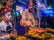 31 DECEMBER 2012 - BANGKOK, THAILAND:  A boy wearing devil's horns looks at grilled meats on street food cart at the New Year's Eve party and countdown in the Ratchaprasong intersection in Bangkok. The traditional Thai New Year is based on the lunar calender and is celebrated in April, but the Gregorian New Year is celebrated throughout the Kingdom, especially in larger cities and tourist centers, like Bangkok, Chiang Mai and Phuket. The Bangkok Countdown 2013 event was called ?Happiness is all Around @ Ratchaprasong.? All of the streets leading to Ratchaprasong Intersection were closed and the malls in the area stayed open throughout the evening.   PHOTO BY JACK KURTZ