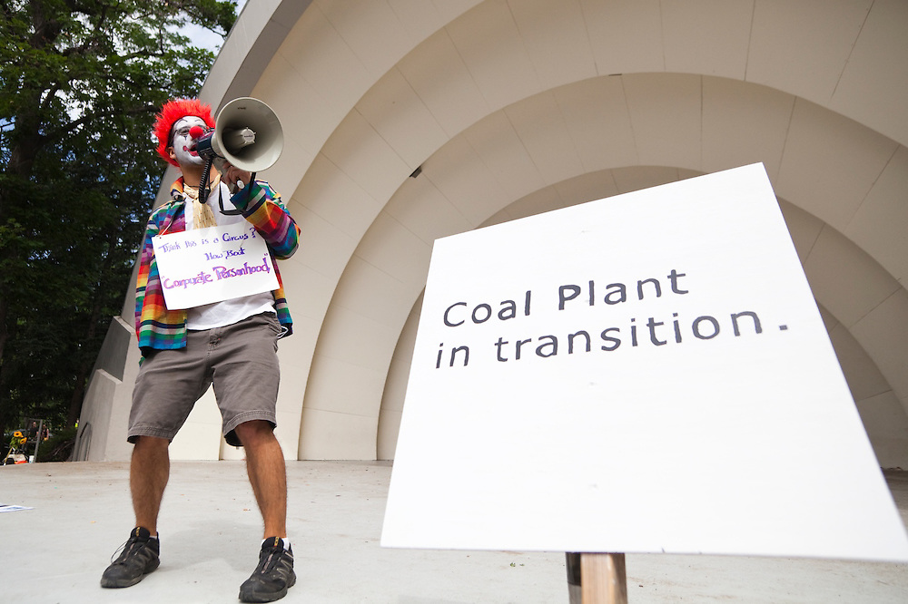 A man dressed as a clown addresses a group of activists preparing to ride bicycles from downtown Boulder, Colorado to the nearby coal-fired Valmont Power Plant to protest its continued operation. The protesters planted sunflowers and erected signs on vacant land outside the entrance to the plant.