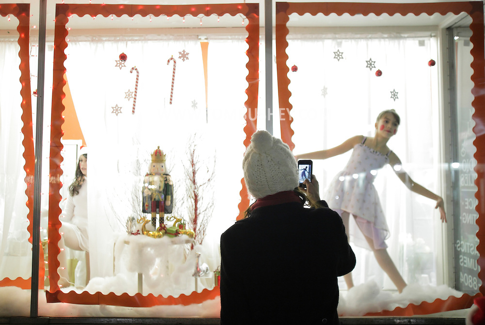 Pine Bush, New York - A woman takes a digital photograph of a dancer from the Mitchell Performing Arts Center posing in a storefront window during the Pine Bush Festival of Lights on Dec. 4, 2010.