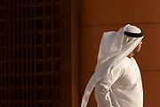 Side view waist up shot of a walking Arab man wearing a thawb, Abu Dhabi, United Arab Emirates