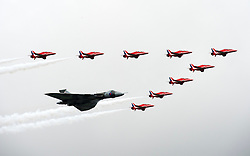 © London News Pictures. 09/07/2012. Farnborough, UK. The Red arrows and the only Vulcan bomber left in service perform a flyby on day one of the Farnborough International Airshow, in Farnborough, Hampshire, UK on July 9, 2012. FIA is a seven-day international trade fair for the aerospace industry which is held every two years at Farnborough Airport . Photo credit: Ben Cawthra/LNP.