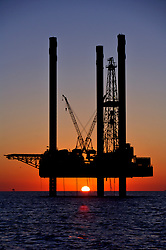 Stock photo of the silhouette of a jack up rig at sunset