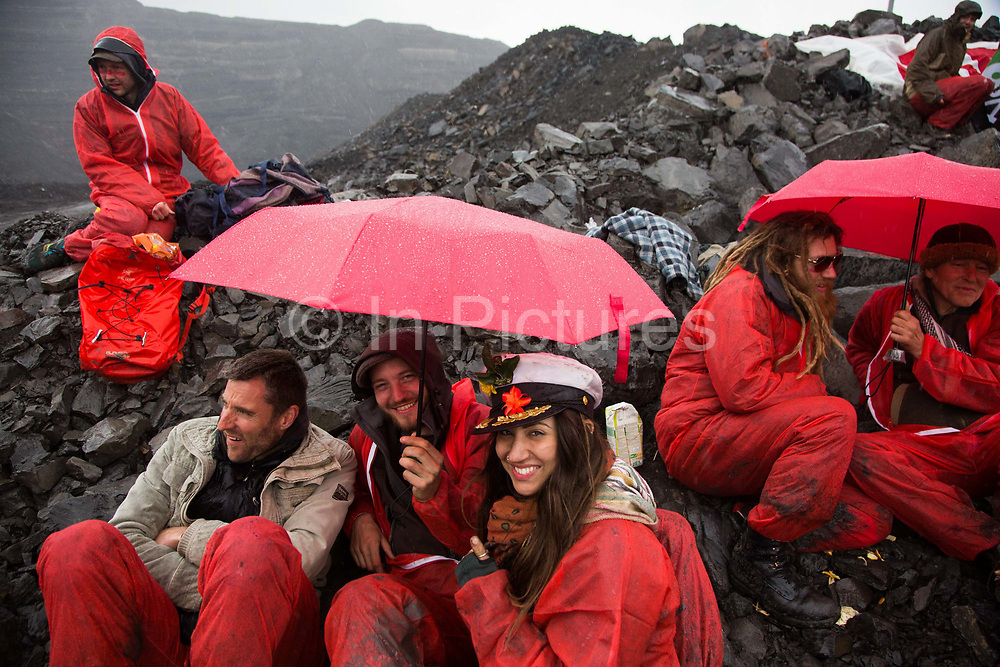 Hundreds of environmental activists stopping the open cast coal mine Ffos-y-Fran near Merthyr Tydfil, Wales from operating May 3rd 2016. As rain set in the symbolic red umbrellas came in handy as shelter. The activists from Reclaim the Power wants the mine shut down and a moratorium on all future open coal mining in Wales. The group Reclaim the Power had set up camp near by and had over three days prepared the action and up to 300 activists all dressed in red went into the mine in the early morning. The activist were plit in three groups and carried various props signifying the red line in the sand, initially drawn in Paris at the COP21. The mine is one of the largest open cast coal mines in the UK and is run by Miller Argent who have to date extracted 5million tons of coal. The activists entered the mine unchallenged by any security or police and the protest went on peacefully till mid afternoon with no arrests made.  Open coal mining is hugely damaging to the local environment and  contributing to global climate change.