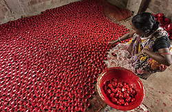Oct. 13, 2017  - Kolkata, India - An Indian potter colors earthen lamps in preparation for Diwali, some 45 km away from Kolkata. Diwali is the Hindu festival of lights which is celebrated on a large scale all over the country. (Credit Image: © Tumpa Mondal/Xinhua via ZUMA Wire)