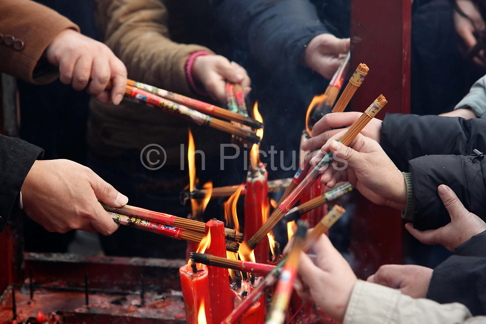 New Year worshippers burn incense at Longhua temple in Shanghai, China on 26 January, 2009.  .Worshippers crowd into Longhua temple to make their Chinese New Year prayers and well-wishes in Shanghai, China on 26 January, 2009.  Traditionally the first day of the lunar new year is an auspicious day to offer prayers and honor ancestors.