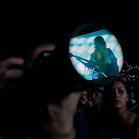 A musician is reflected on the lens of a photographer in the audience as Prince performs during his concert on Sziget festival held in Budapest, Hungary on August 09, 2011. ATTILA VOLGYI