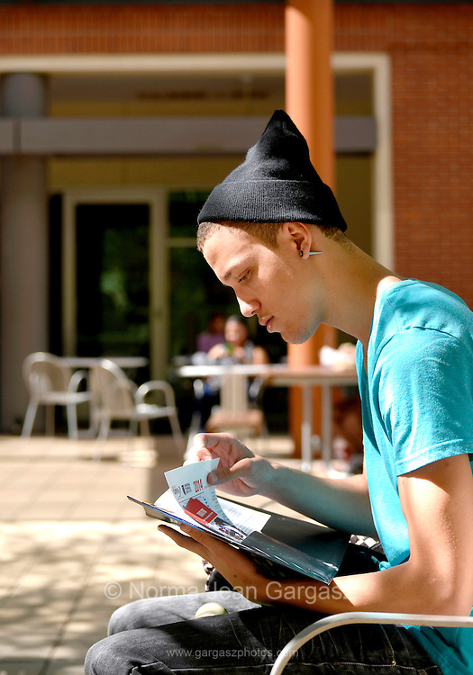 A young man on a college campus looking through educational brochures.