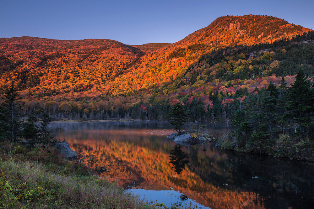 First light on fall foliage hillsides and reflections in pond, White Mountain National Forest, Woodstock, NH
