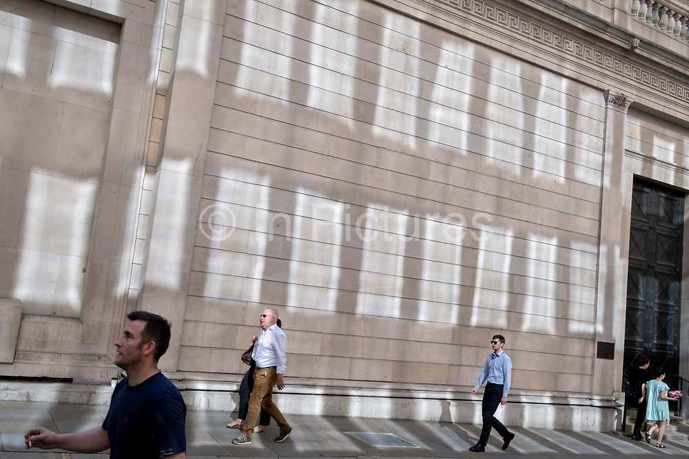 In the week that many more Londoners returned to their office workplaces after the Covid pandemic, City workers walk past sun reflections on the walls of the Bank of England in the City of London, the capitals financial district, on 8th September 2021, in London, England.