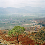 Landscape view looking towards a valley in the northern mountainous part of Yunnan province showing winding roads and fallow fields.