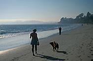 Woman walking dog on sand during day, Butterfly Beach, Santa Barbara, California