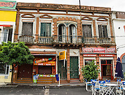 """An old building with balconies and streetside cafe. In La Boca barrio (neighborhood) of Buenos Aires, tourists are attracted by colorful houses, the Caminito pedestrian street, La Ribera theatre, tango clubs, and Italian taverns. La Boca retains a strong European flavor, with many early settlers from Genoa, Italy. It sits at the mouth (""""boca"""" in Spanish) of the Matanza River (or Río Mataderos, or Riachuelo which simply means ?Creek?). La Boca is known among sports fans for La Bombonera stadium (Estadio Alberto J. Armando), home of Boca Juniors, one of the world's best known football (soccer) clubs. As a centre for radical politics, La Boca elected the first socialist member of the Argentine Congress (Alfredo Palacios in 1935) and hosted many demonstrations during the crisis of 2001 in Argentina, South America."""