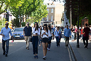 People heading to the market pass past the colourfully painted houses on Portobello Road in Notting Hill, West London, England, United Kingdom. People enjoying a sunny day out hanging out at the famous Sunday market, when the antique stalls line the street.  Portobello Market is the worlds largest antiques market with over 1,000 dealers selling every kind of antique and collectible. Visitors flock from all over the world to walk along one of Londons best loved streets.