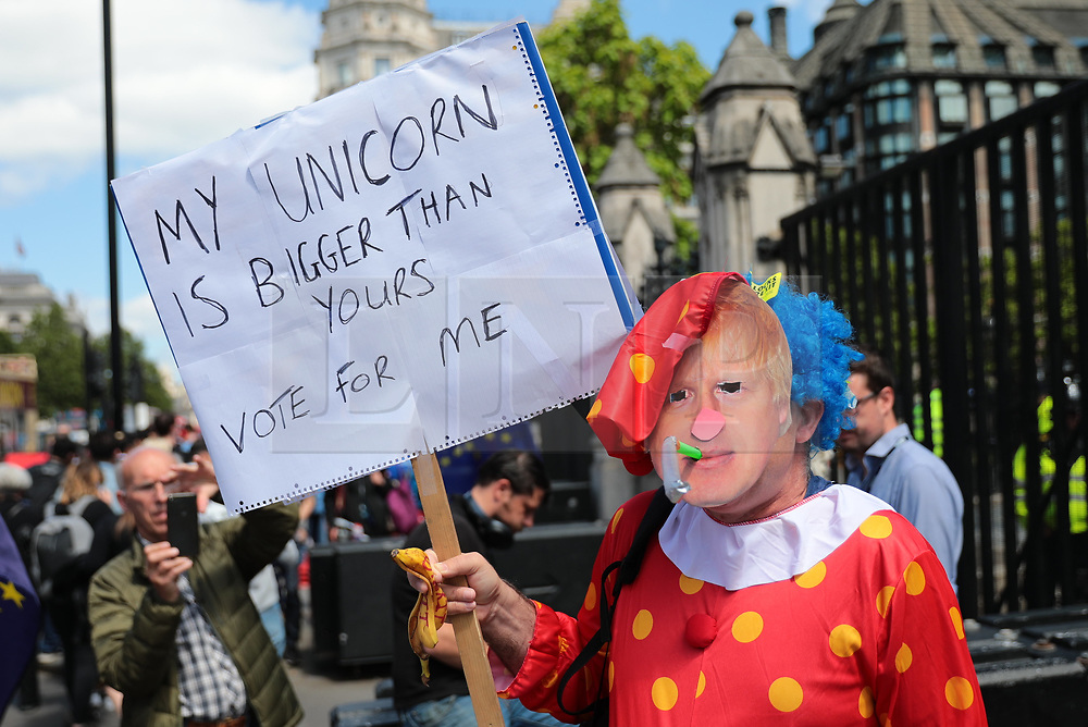 © Licensed to London News Pictures. 17/06/2019. London, UK. A protester dressed as a clown with a Boris Johnson mask stands outside Parliament. A second round of voting on the Conservative Party leadership contest will take place tomorrow. Photo credit: Rob Pinney/LNP