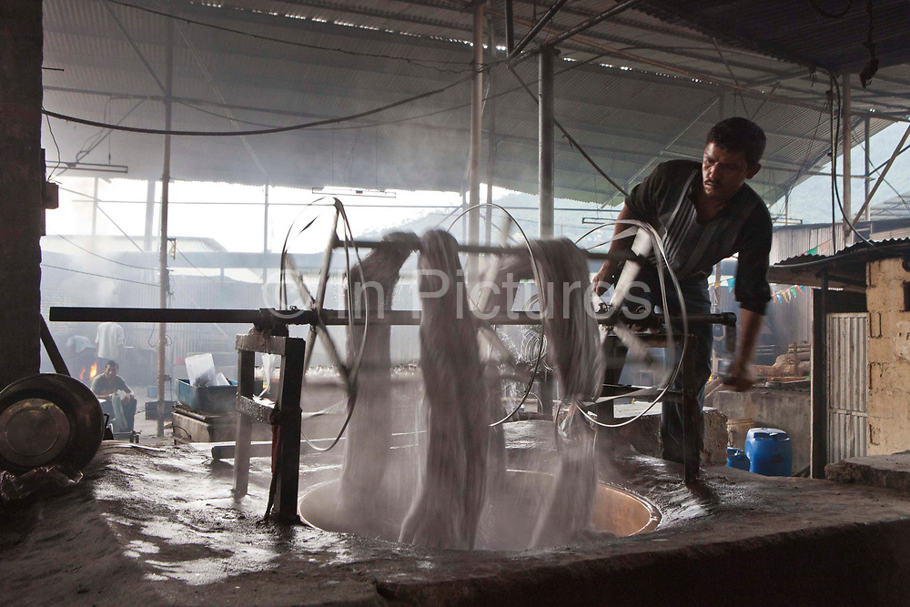 A Nepalese factory worker rotates the metal frame which coils the wool yarn and feeds it through dye mixture, which is heated from below by the fire. It is just one part of the rug making process at R.C rug factory in the Narayanthan area of Kathmandu, Nepal. The company export rugs and carpets to Europe the U.S and Canada, and rely on the GoodWeave certificate of approval to boast excellent quality and fair conditions for its workers, as the carpet factory industry in Nepal is notorious for providing poor working conditions and forcing young children into labour.