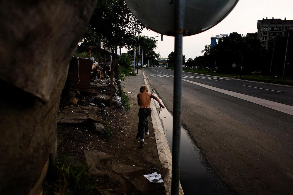 Boy playing along the road that forms the western border of Nova Gazela.