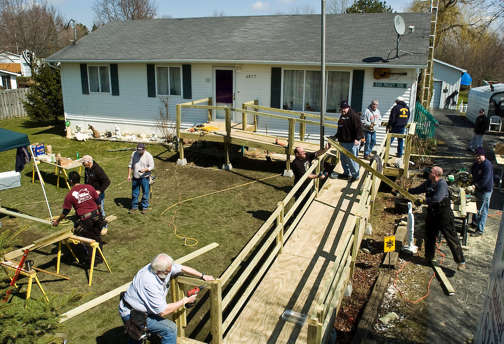 Matt Dixon | The Flint Journal..Volunteers from Genesee County Habitat for Humanity and the Burton Fire Department work to build a ramp for 77-year-old Army Veteran Charles Burnett outside his home in Burton. The project was one of three ramps for veterans that were funded through a grant from State Farm Insurance.