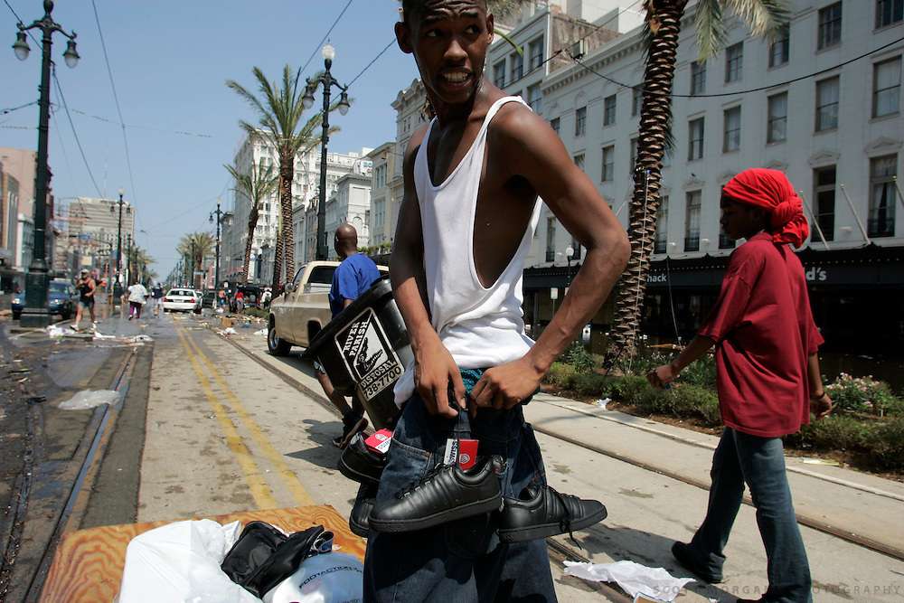 A man ties tennis shoes to his belt Wednesday, August 31, 2005, on Canal Street in New Orleans, La. The New Orleans police were largely letting looters take what they wanted, stopping them only when they needed the goods themselves. Scott Morgan