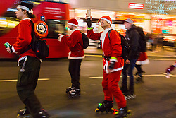 London, December 23 2017.A horde of rollerblading Santas skate down Oxford Street as shoppers crowd London on the second last shopping days before Christmas. © Paul Davey