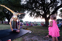 Girl in pink dress watching people practicing yoga and acrobatic moves at July 4th celebration on the Trinity Trails near the Panther Island Pavilion, Trinity River, Fort Worth, Texas, USA.