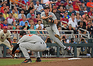 Infielder Michael Gretler #10 of the Oregon State Beavers makes a throw to first for an out in the sixth inning against the Arkansas Razorbacks during game three of the College World Series Championship Series at TD Ameritrade Park in Omaha, Nebraska.
