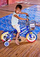 Little boy at Nanga Sumpa longhouse shows off his new bike.