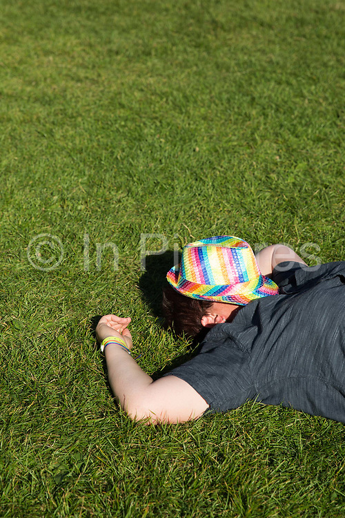 A person asleep on the grass with a rainbow trilby hat covering their face during the Brighton Pride festival on 6th August 2016 in Brighton in the United Kingdom.