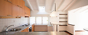 Front view of vintage kitchen with wooden furniture. On the ceiling white wooden beams