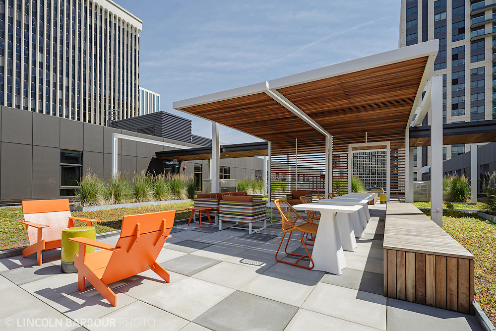 An outdoor common space sits between two high rise buildings.  It is decorated with bright furniture.  Very clean and modern looking.