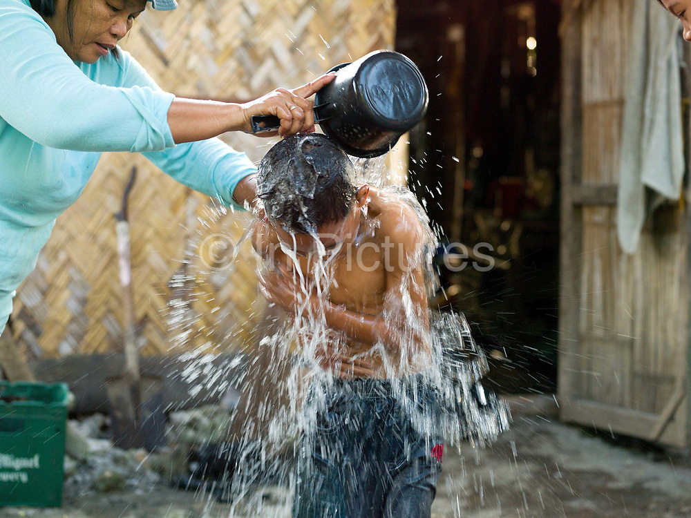 Jilena Pineda (50) washes her son before school, Barangay Numo, Esperanza, Sultan Kudarat province, Mindanao Island, The Philippines.