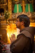 A young monk inside Interior of iglesia de san Francisco Quito, Ecuador, South America
