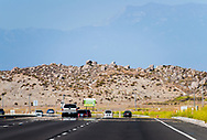 Cars drive down a newly paved highway through the Southern California desert, toward hazy mountains