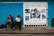 Two central american migrants sit next to a banner that denounces that, from 2009 to 2011, 20 thousand migrants have been kidnapped by organised crime, who earn anually for this, 50 000 million US Dollars. (Photo: Prometeo Lucero)