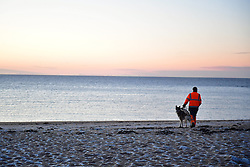 © Licensed to London News Pictures. 13/01/2017. Jaywick, UK. The sea looks calm as a man walk his dog along on the seafront at Jaywick before Homes are evacuated in Jaywick, Essex  due to the threat of flooding in low-lying areas . Photo credit: Ben Cawthra/LNP