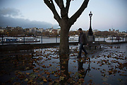 A man prepares to jump over Autumn leaves in a puddle of rain water on the Southbank riverside walkway, London, United Kingdom. The South Bank is a significant arts and entertainment district, and home to an endless list of activities for Londoners, visitors and tourists alike.