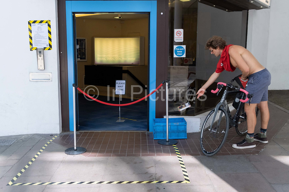 A cyclist throws a library book into a book drop-off box outside Shoe Lane Library during the Coronavirus pandemic in the City of London, the capitals financial district, on 6th August 2020, in London, England.