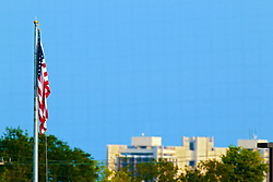 23 August 2014:  The American Flag flies over CornCrib stadium with ISU's Waterson Towers in the background during a Frontier League Baseball game between the Traverse City Beach Bums at Normal CornBelters at Corn Crib Stadium on the campus of Heartland Community College in Normal Illinois