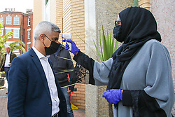 © Licensed to London News Pictures. 30/04/2021. London, UK. Sadiq Khan, Mayor of London, wearing a face covering has his temperature checked as he arrives to joins muslim devotees for Friday prayers during the Islamic holy month of Ramadan at the London Islamic Cultural Society and Mosque, also known as Wightman Road Mosque in Haringey, north London. The Mayor of London and the devotees are two meters apart and keeping to the rules of social distancing. Muslims across the world are observing the holy fasting month of Ramadan, a month long celebration with prayers, readings from the Koran and meeting with family and friends, as they abstain from eating, drinking and smoking from dawn till dusk. Sadiq Khan is running for re-election as London Mayor. Photo credit: Dinendra Haria/LNP