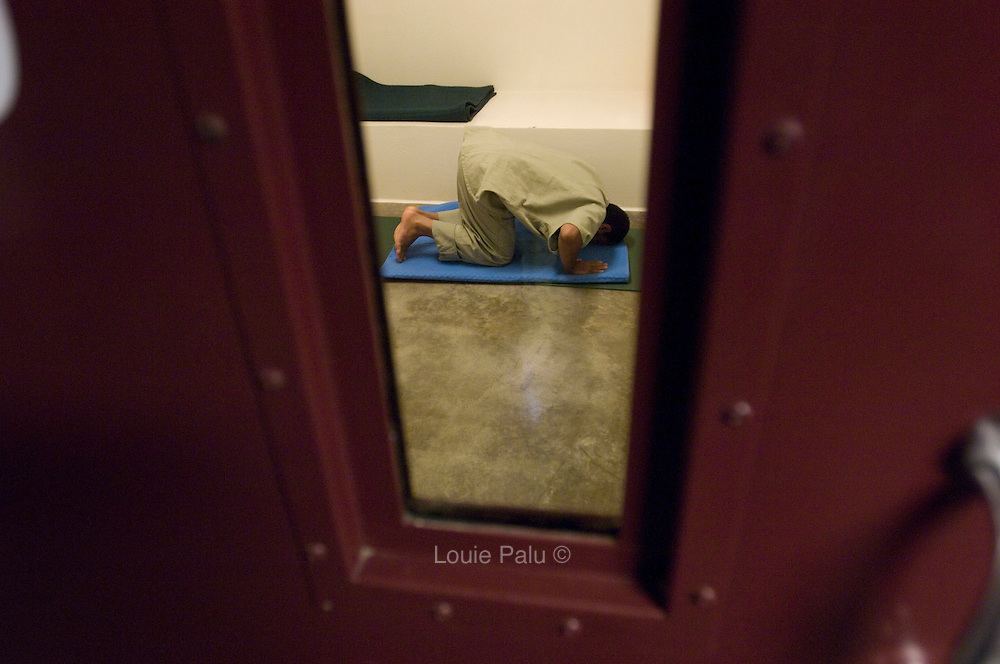 """A detainee prays in his cell in Camp 5, which is a maximum-security detention facility where the most uncooperative as well as detainees with the most intelligence value are housed at the detention facility in Guantanamo Bay, Cuba. Approximately 250 """"unlawful enemy combatants"""" captured since the September 11, attacks on the United States continue to be held at the detention facility. (Image reviewed by military official prior to transmission)"""