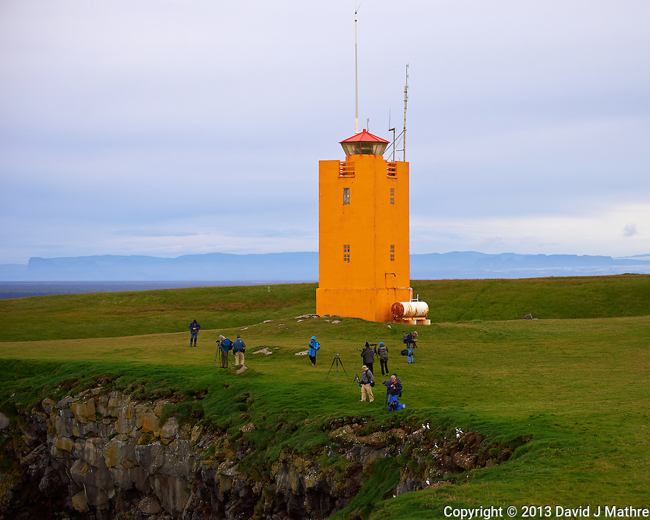 Lighthouse, Photographers, and Puffins on the Cliff at Cape Ingolfshofdi (Ingólfshöfði). A private nature preserve on an isolated headland on the coast half way between Skaftafell in Vatnajokull National Park and Jökulsárlón ice lagoon in Iceland. Composite of 3 images taken with a Nikon D4 camera and 80-400 mm VRII lens (ISO 250, 80 mm, f/4.5, 1/1000 sec). Nikonians Academy Iceland Photo Adventure.