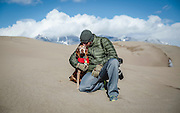 SHOT 12/30/15 1:51:24 PM - Marc Piscotty of Denver, Co. pauses for a picture with his dog, Tanner, an 11 year-old male Vizsla, at Great Sand Dunes National Park and Preserve. Great Sand Dunes is a U.S. National Park located in the San Luis Valley, in the easternmost parts of Alamosa County and Saguache County, Colorado, United States. Originally created as Great Sand Dunes National Monument on March 17, 1932, Great Sand Dunes National Park and Preserve was established by an act of the United States Congress on September 13, 2004. The park contains the tallest sand dunes in North America, rising about 750 feet (230 m) from the floor of the San Luis Valley on the western base of the Sangre de Cristo Range, covering about 19,000 acres. Researchers say that the dunes started forming less than 440,000 years ago. The dunes were formed from sand and soil deposits of the Rio Grande and its tributaries, flowing through the San Luis Valley. Over the ages, glaciers feeding the river and the vast lake that existed upon the valley melted, and the waters evaporated. Westerly winds picked up sand particles from the lake and river flood plain. As the wind lost power before crossing the Sangre de Cristo Range, the sand was deposited on the east edge of the valley. This process continues, and the dunes are slowly growing. The wind changes the shape of the dunes daily. (Photo by Marc Piscotty / © 2015)