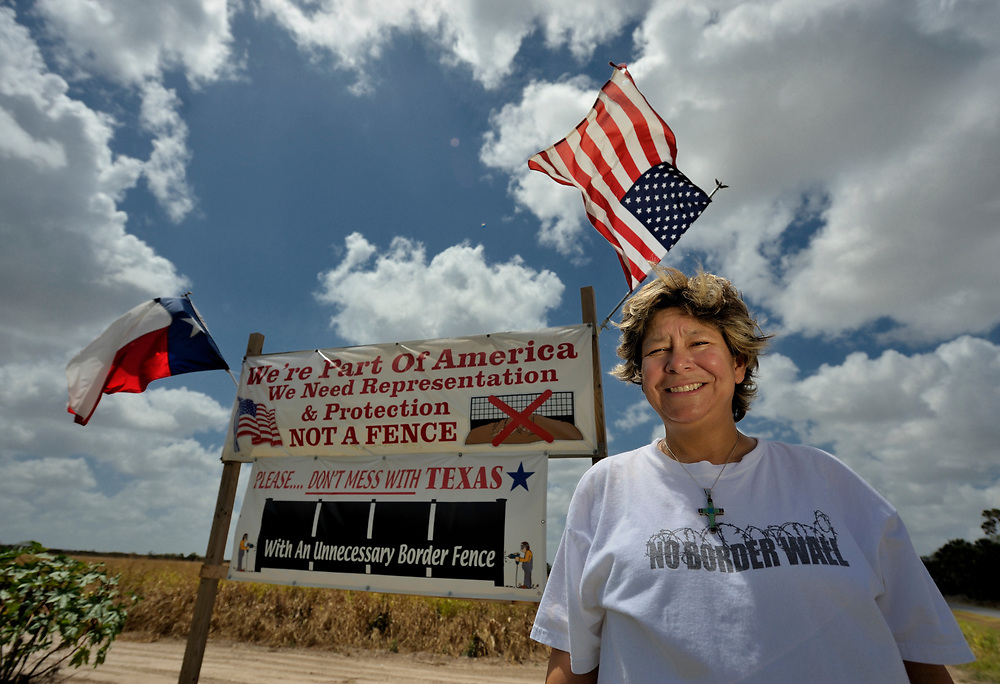 Cindy Johnson, a United Methodist deaconess in Brownsville, Texas. Active in immigration issues, Johnson here stands by a protest sign near the route of a wall being built along the U.S.-Mexico border.